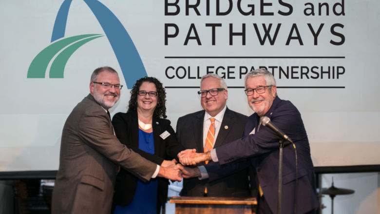 Four college presidents shake hands on stage.