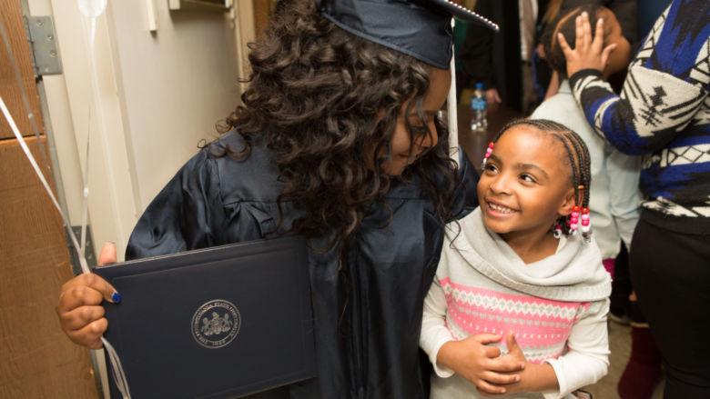 Graduate Taejsha McBride hugs her daughter.