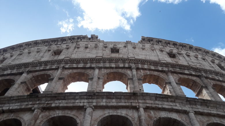 A view of the Colosseum against blue sky.