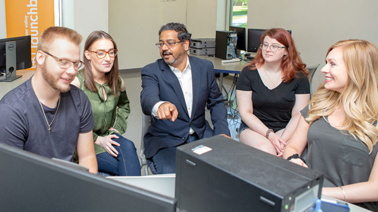 Ashu Kumar works with four students at a computer station.