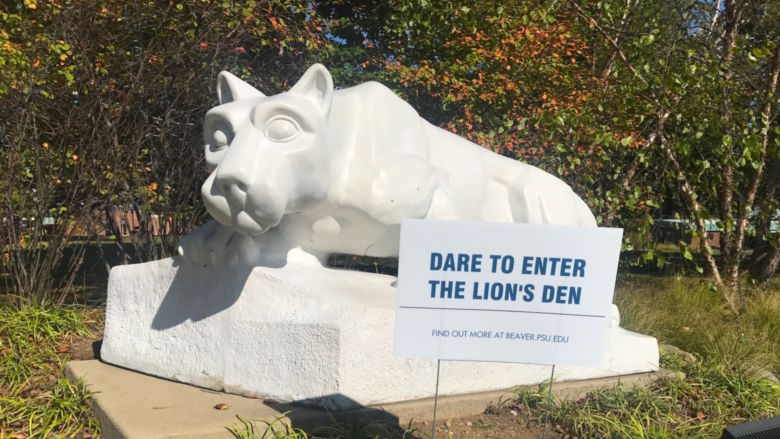 Dare to enter the Lion's Den sign sits in front of lion shrine.