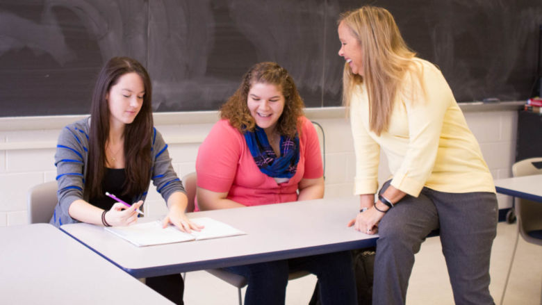 Karen Barr, right, talks with two students in a Penn State Beaver classroom.