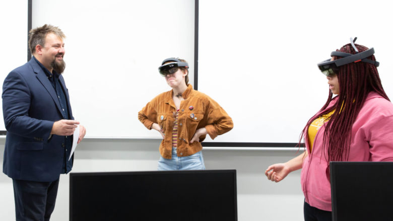 The professor stands to the left as two female students wear goggles as part of a classroom experiment.