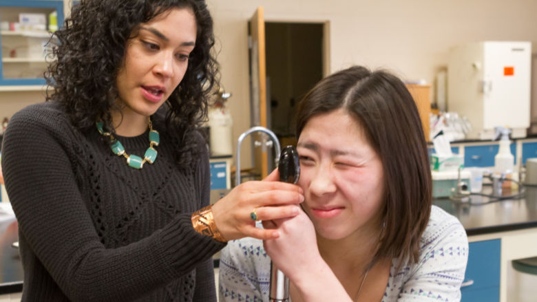 Professor Stephanie Cabarcas-Petroski holds an ophthalmoscope up to a student's eye.