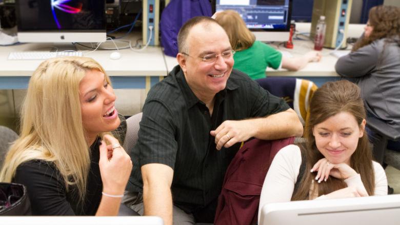 John Chapin and two students look at a computer screen.