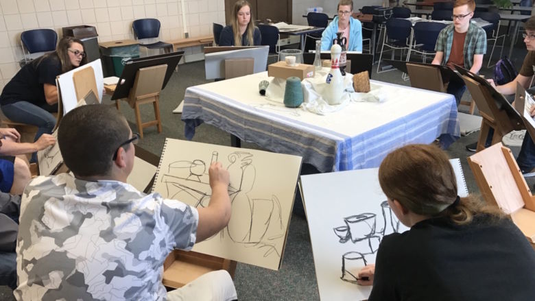 Students sit on drawing horses and sketch a still life with charcoal.