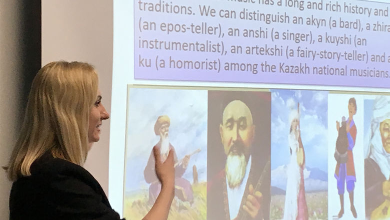 A blonde woman wearing a dark jacket stands to the left of a screen displaying information about Kazakhstan.
