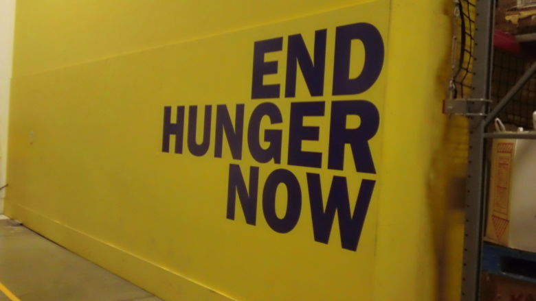 "Shot of a wall at the Greater Pittsburgh Community Food Bank that reads ""End Hunger Now."""