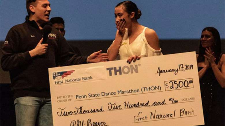 Hailey Burbage covers her mouth with her hand and reacts with emotion as she accepts a big check for winning the THON Showcase.
