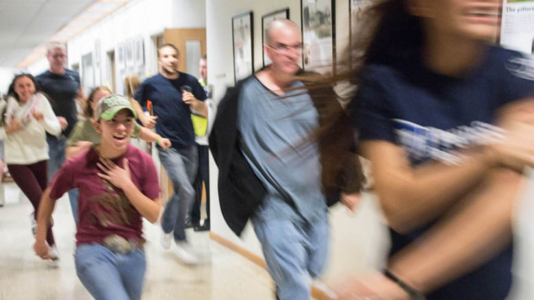 Student actors run down a hallway.