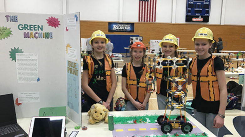 Four girls stand in front of a table wearing bright construction vests and yellow construction hats.
