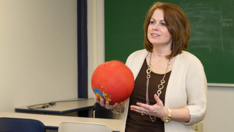 Michelle Kurtyka holds a ball in a classroom in the gymnasium