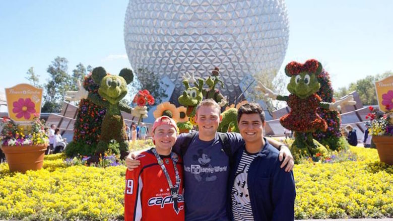 Nick Pelino and two of his roommates stand in front of a topiary display.
