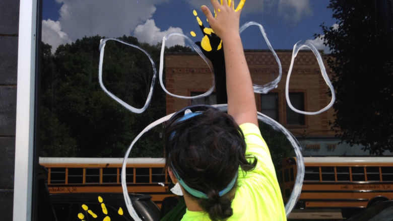 Sophomore Nick Pelino paints a handprint on a window.