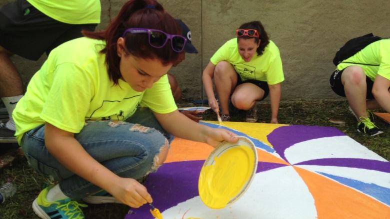 Penn State Beaver freshman Nicole Pastorino paints a wooden pallet.