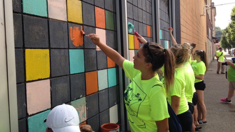 Members of the volleyball and softball teams paint bricks on a building in Aliquippa.