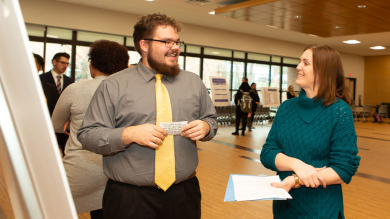 Mari Pierce speaks with a student while judging his research project.