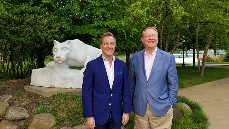 Two men wearing blazers stand in front of the Nittany Lion Shrine at Penn State Beaver.