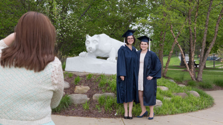 Jessica Findling and a friend pose in their caps and gowns in front of the Lion Shrine.