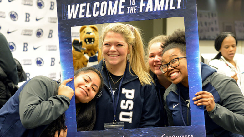 Three female students pose for while holding a large Penn State Welcome picture frame.