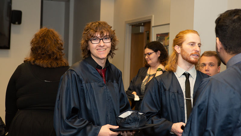 Penn State Beaver graduates wearing gowns talk after ceremony.