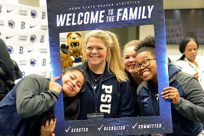 Three female students pose for a photo while holding a Penn State Welcome picture frame around themselves.