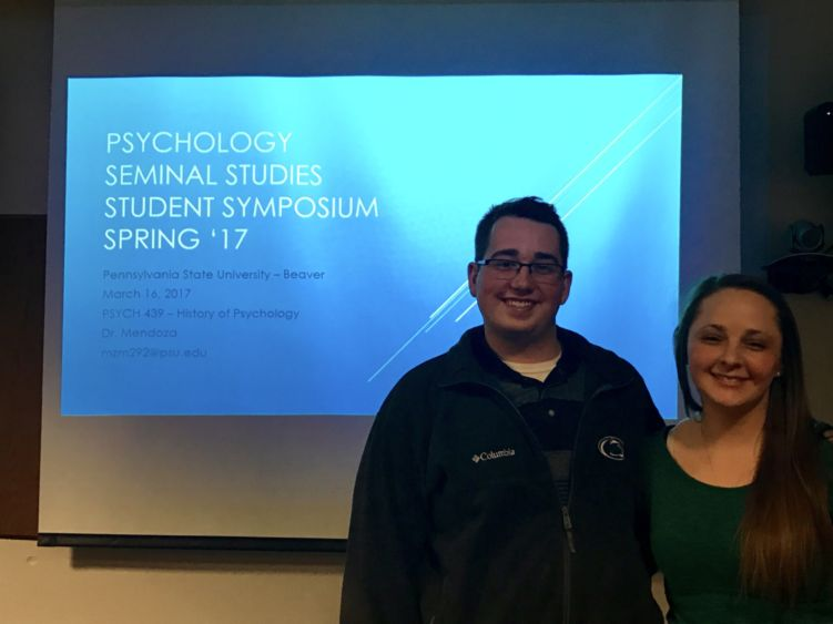 Two of Marissa Mendoza's Psych 439 students pose in front of a screen.