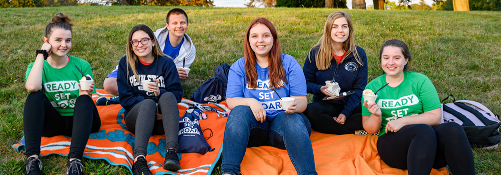 Six students dressed in shirts that say ready, set, roar sit on the ground with ice cream.
